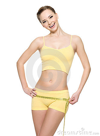 Laughing woman with health body measuring hips