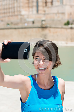 Laughing woman photographing herself