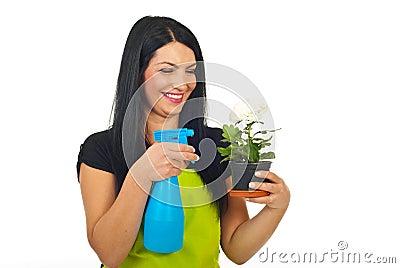 Laughing woman spraying flower in pot