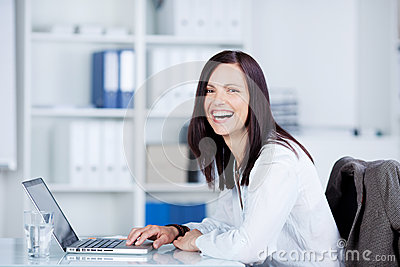 Laughing woman using a laptop