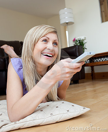 Laughing woman watching TV lying on the floor