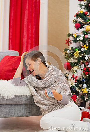 Laughing woman watching TV near Christmas tree
