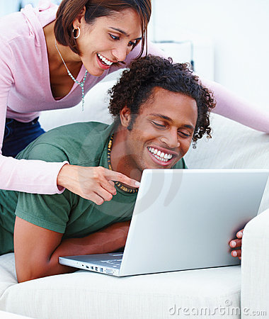 Laughing young couple looking at laptop in home