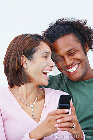 Laughing young couple texting a message