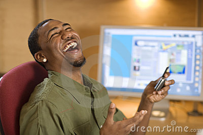 Laughing young man with cell phone and computer