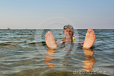 Young man floats in water with feet up