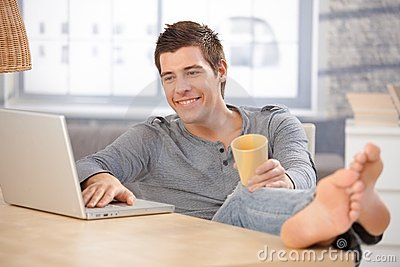 Laughing young man using computer at home