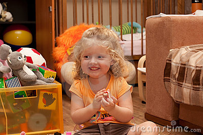 Lauhging girl on the floor in nursery room