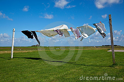 Laundry drying on clothes line against a blue sky