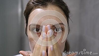 Lavado de cara - una chica aplica espuma facial en su piel mientras mira la cámara Cosméticos naturales de origen natural metrajes