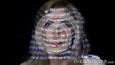 Lavoratore femminile biondo attraente del computer che sfrega con i codici binari mentre i dati digitali sono proiettati sul suo  stock footage