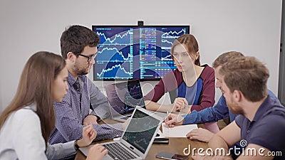 Lavoratori del dipartimento finanziario della grande azienda siedono in ufficio e si riuniscono, visualizzano diagrammi stock footage