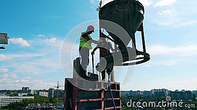 Lavoratori in piedi sul palazzo con una cisterna di cemento video d archivio