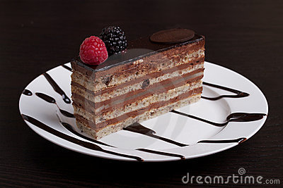 ... chocolate cake topped with a raspberry and blackberry on a white plate
