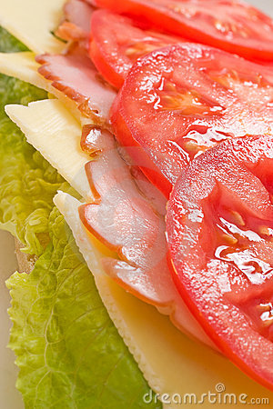 Layered lettuce, cheese, ham and tomatoes sandwich