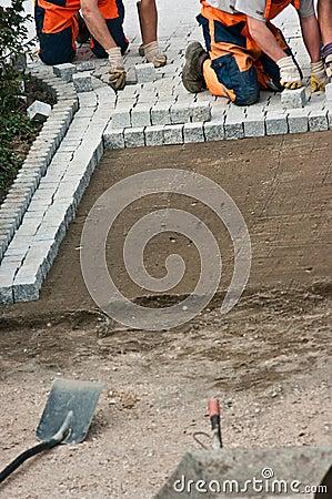 Laying paving bricks on soil