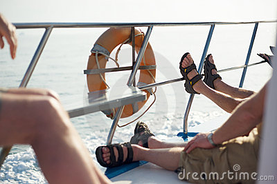 Lazy boat trip with sandals on railing