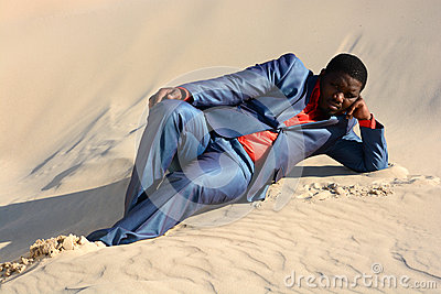 Lazy businessman laying in sand
