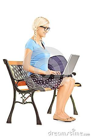 Lächelnde blonde Studentin, die auf einer Bank und einem Arbeiten sitzt