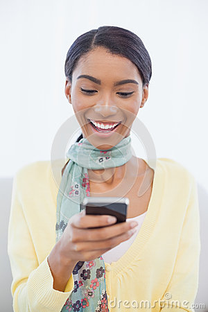 Lächelnde elegante Frau, die auf Sofaversenden von sms-nachrichten sitzt