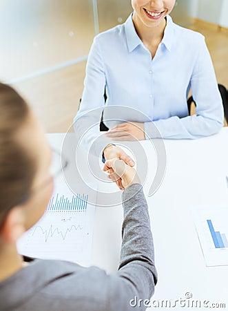 Lächelnde Geschäftsfrau zwei, die Hände im Büro rüttelt