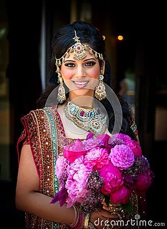 Lächelnde indische Braut mit Blumenstrauß