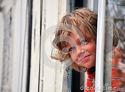 Lächelnder Junge, der heraus schaut
