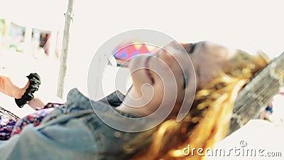 Le balancement heureux de jeune fille dans l'hamac sur la plage sourient in camera Jour ensoleillé insousiant banque de vidéos