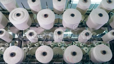 Le bobine con i fili girano su uno scaffale in una pianta tessile linea di produzione industriale del tessuto video d archivio