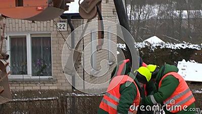 Le camion et les travailleurs d'enlèvement d'eaux d'égout avec le grand tuyau sucent des résidus de la rue bien clips vidéos
