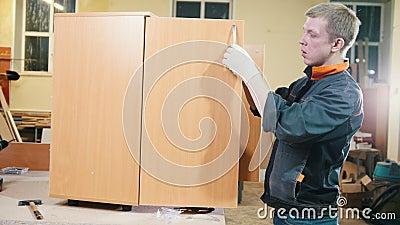 Le charpentier de travailleur visse des garnitures dans le coffret à une usine de meubles banque de vidéos