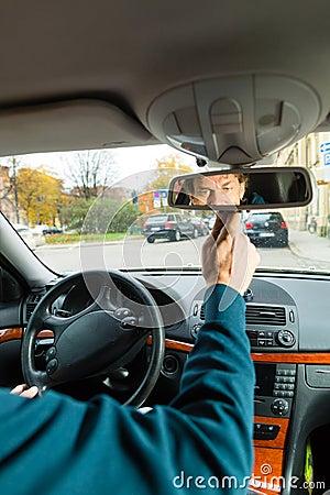 Le chauffeur de taxi regarde dans le miroir pilotant