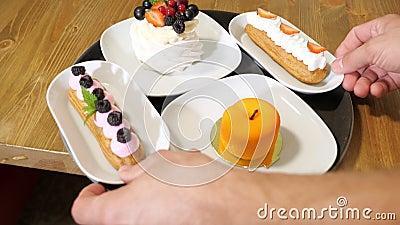 Le confiseur transporte de savoureux gâteaux aux clients qui attendent au café banque de vidéos