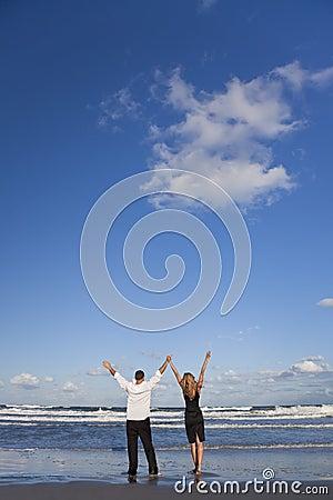Le coppie che celebrano le braccia si sono alzate su una spiaggia
