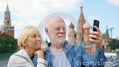 Le coppie senior sulla discesa del ` s del basilico fanno il selfie sul telefono cellulare Viaggio dei pensionati a Mosca, Russia video d archivio