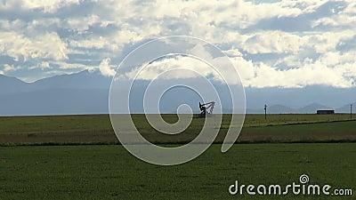Le cric éloigné de pompe extrait l'huile parmi le champ frais contre des nuages banque de vidéos