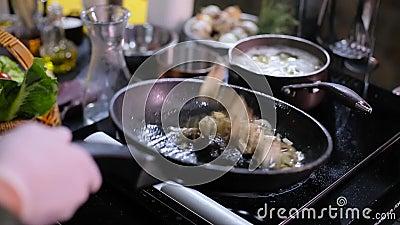Le cuisinier fait frire des champignons dans une casserole clips vidéos