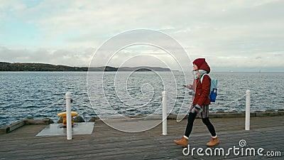 Le donne che viaggiano usano l'app Smartphone App Walking al Sea Wooden Dock il giorno dell'autunno video d archivio