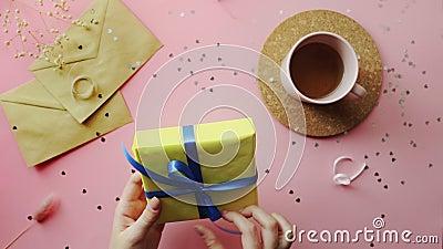 Le donne legano un regalo di Natale avvolto in carta gialla con arco blu Vista dall'alto sul tavolo rosa di legno, lastra piatta video d archivio