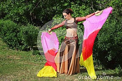 Le femme danse avec des ventilateurs de voile