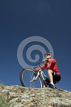 Le femme sur la bicyclette de montagne