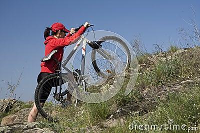 Le femme sur une bicyclette de montagne