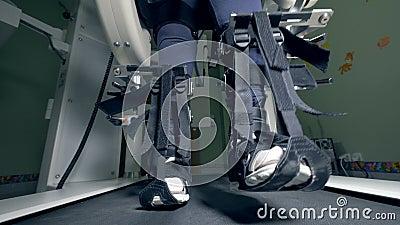Le gambe di una persona fisicamente sfidata legata con le cinghie stanno muovendo lungo la pista di camminata stock footage