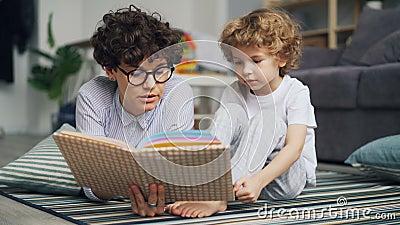 Le garçon adorable d'enfant écoute le conte de fées tandis que la maman lit l'histoire à la maison clips vidéos