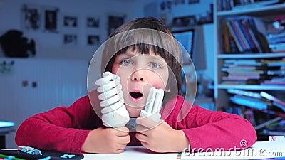Le garçon joue avec deux ampoules économes en énergie banque de vidéos
