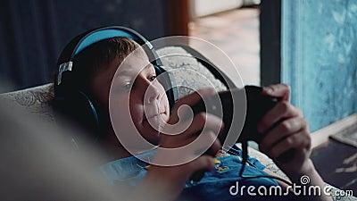 Le garçon joue un jeu vidéo se trouvant sur le divan avec un casque sur sa tête Assez plan rapproché Divertissement de multim?dia banque de vidéos