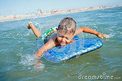 Le garçon a l amusement avec la planche de surf