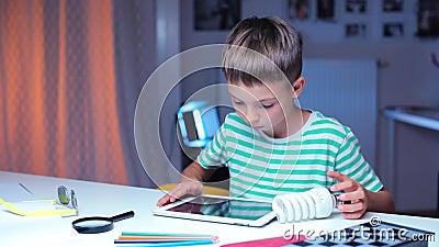 Le garçon utilise une tablette lorsqu'il est assis à une table, examine une ampoule économe en énergie banque de vidéos