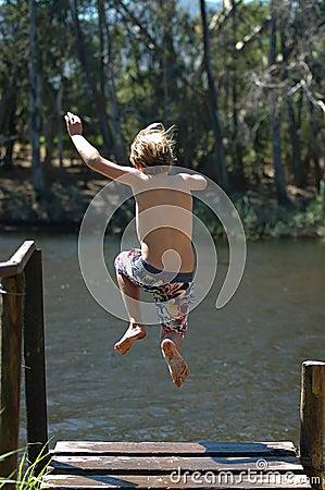 Le garçon sautant dans le lac