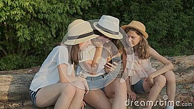 Le groupe d'enfants, trois filles s'asseyant dessus ouvre une session la nature et regarder le smartphone banque de vidéos